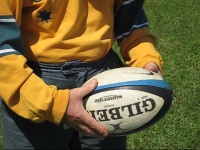Player shows a grip to spin pass a rugby ball