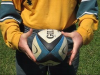 Player shows how to spin a rugby ball. Step 2.