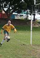 Player practices chip kick at rugby posts